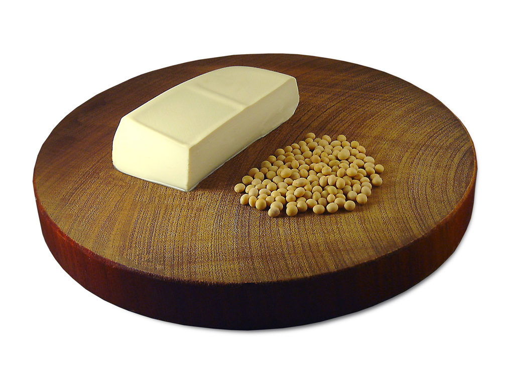 Tofu and soybeans on a wooden cutting board